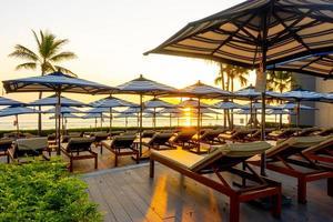 Sombrilla y sillón alrededor de la piscina al aire libre en el hotel resort para viajes vacaciones vacaciones foto