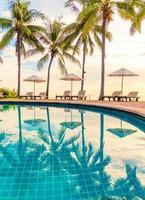 sombrilla y silla alrededor de la piscina en el hotel resort para viajes de placer y vacaciones cerca del mar océano playa foto