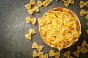 Secar pasta farfalle cruda en un tazón foto