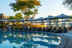 Sombrilla y cama de piscina alrededor de la piscina al aire libre en el hotel resort para viajes vacaciones vacaciones foto