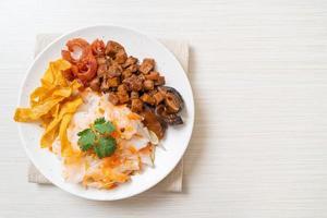 Fideos chinos de arroz al vapor con cerdo y tofu en salsa de soja dulce foto