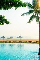 sombrilla y silla alrededor de la piscina con vista al mar foto
