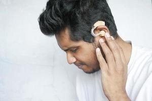 Hearing aid concept, a young man with hearing problems photo