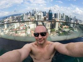 Selfie on man with Kuala Lumpur in background photo