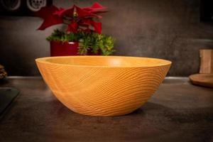 A turned rustic light wooden bowl stands on a dark surface photo