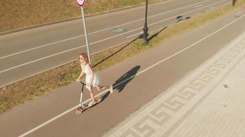 photo aérienne d'une femme chevauchant un scooter à l'extérieur dans une journée d'été video