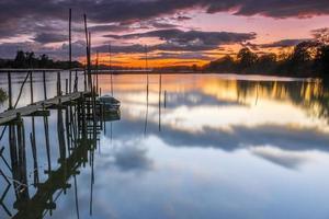 Barco en el río con aguas tranquilas al atardecer foto