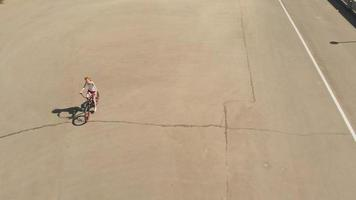 Young woman riding a bicycle outdoors in summer River embankment Friendlily transport Aerial shooting video