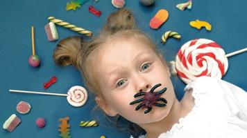 Cheerful little girl lies on a blue background with sweets Closeup portrait video
