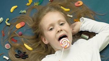 Little girl with a lollipop lies on a blue background Closeup portrait top view video