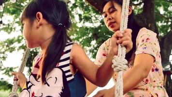 Happy mother pushing laughing daughter on swing in summer park. Family spend time together on vacation. video