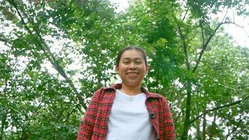 Portrait of a happy young woman looking at camera and smiling in a nature park . Travel and happiness concept. video