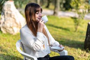 niña bebiendo una taza de té en el jardín foto