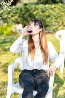 girl drinks goblet of red wine in the garden photo