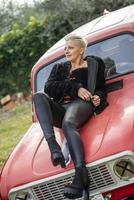 portrait short hair blonde girl lying on top of a car photo
