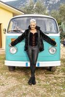 Retrato de chica rubia de pelo corto apoyado contra una furgoneta vintage foto
