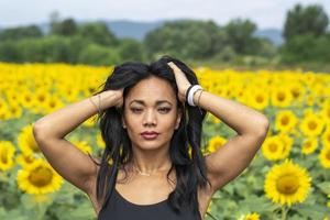 Indian girl sniffing a sunflower flower photo