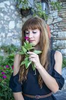 a long haired girl sniffing flowers photo