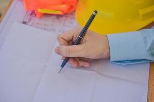 Cerrar el diseño del dibujo del ingeniero en el papeleo en la oficina foto