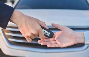 Hand giving key car business sale rent insurance photo