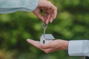 Hand giving key house business sale rent insurance photo