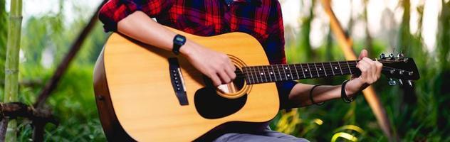 guitarra y hombre, el joven guitarrista toca alegremente la música. foto