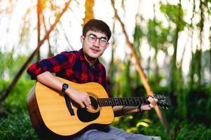Man playing guitar outside photo