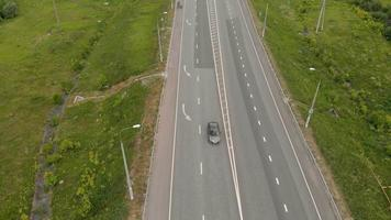 The movement of cars on the highway in the vicinity of the village Aerial footage video