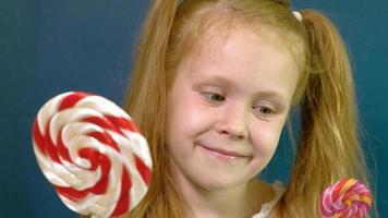 kleines Mädchen mit einem Lutscher auf blauem Hintergrund Nahaufnahme Porträt video