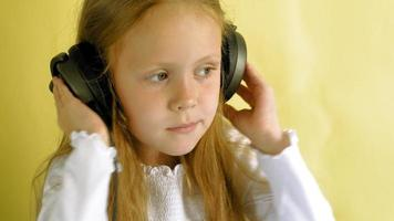 Cheerful little girl in headphones on a yellow background Closeup portrait video