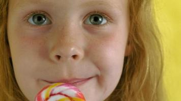 Little girl with a lollipop on a Yellow background Close up portrait video
