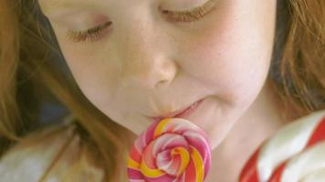 Little girl with a lollipop on a blue background Close up portrait video