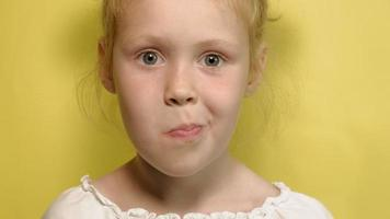 Cheerful little girl on a yellow background with color jelly Closeup portrait video