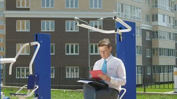 empresário sentado em um campo de esportes ao ar livre video