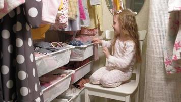 hermosa niña en el armario de la casa. niños de moda video