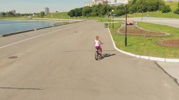 jovem andando de bicicleta ao ar livre no verão rio dique transportar, amigavelmente, tiro aéreo video