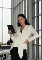 Candid portrait of young caucasian confident businesswoman  using tablet to work in office photo