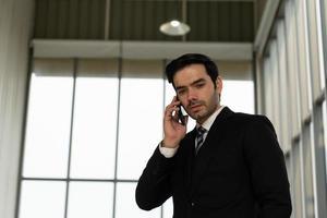 Sincero retrato de joven apuesto hombre de negocios caucásico confiado en traje negro con corbata, utilizando el teléfono inteligente para hablar con el cliente en la oficina foto