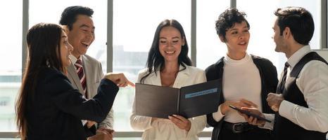imagen de banner del equipo de negocios internacionales que incluye personas caucásicas y asiáticas de pie junto a la ventana en la oficina y discutiendo sobre el proyecto. diversidad en el concepto de negocio foto