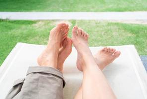 Cerrar descalzo de pareja lgbt tumbados juntos en el banco en el jardín foto