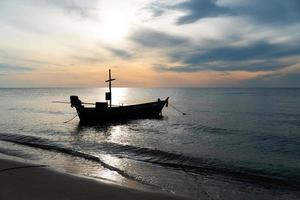 Silueta de un pequeño barco de pesca en el mar al amanecer. foto