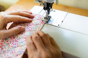 Close up of woman sewing fabric photo
