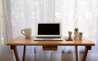 escritorio de trabajo que incluye computadora, taza de café, teléfono inteligente en la sala de estar foto