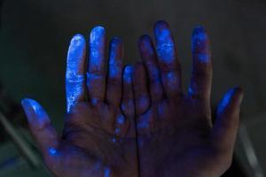 manos cubiertas de polvo bajo una luz negra foto