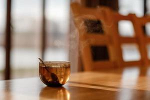 Cup of tea with steam on wooden table in the living room. selective focus photo