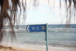 cartel de inodoro en la playa foto