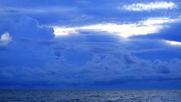 dark storm cloud on sea and cargo ship is parking on horizon video