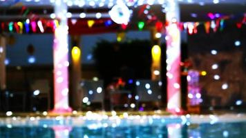 Reflection Blurred and bokeh dancing blue lights of party at luxury pool side video