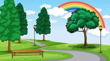 Park landscape scene with rainbow in the sky vector