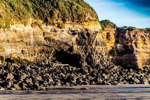colinas y formaciones rocosas en la playa de opunaki. opunaki, nueva zelanda foto